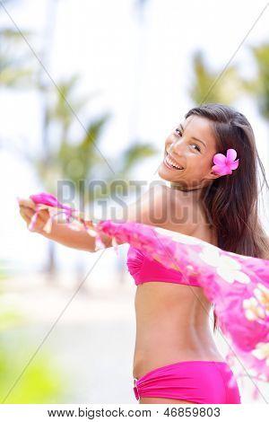Natural beauty ethnic woman happy on beach waving pink scarf in joy. Beautiful joyful girl on summer vacation travel holiday on Big Island, Hawaii, USA. Gorgeous pretty mixed race female bikini model.