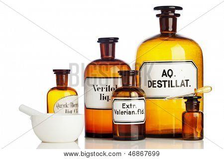 Viejas botellas de farmacia, cuentagotas, mortero y Maja aisladas en blanco