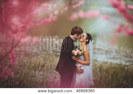 happy bridal couple in park