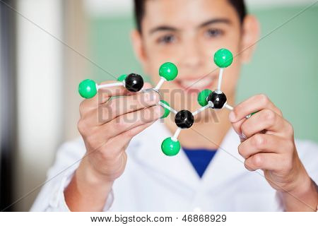 Closeup of schoolboy examining molecular structure in lab