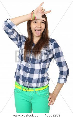 Teenage Girl Shows Tongue And Makes Hand Horns. Mint-colored Pants And A Plaid Shirt.
