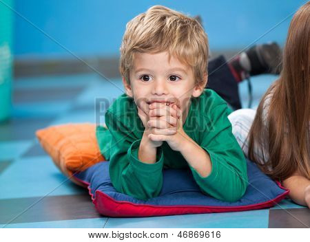 Happy little boy with hands clasped lying on floor with classmate in kindergarten
