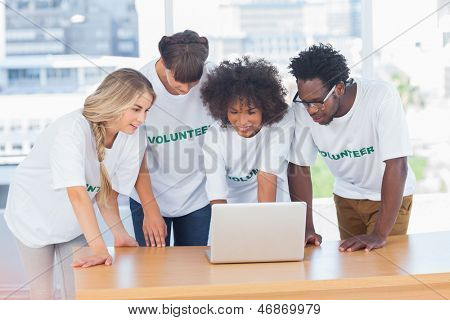 Volunteers working together on a laptop in their office