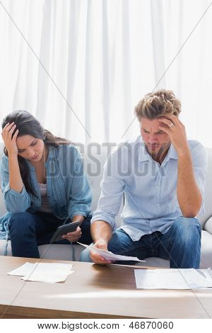 Upset couple doing their accounts in the living room
