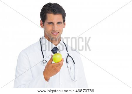 Doctor holding an apple and smiling at camera on a white background