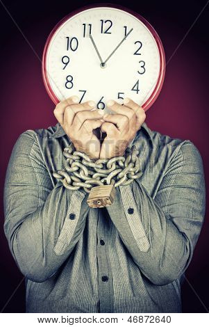 Formally dressed man holding a clock in place of his face with his hands chained with a metallic chain and padlock (useful to illustrate overworked  or stressed people)