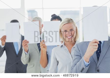Business team covering face with white paper except for one woman smiling at camera