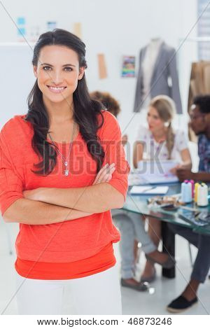 Pretty fashion designer with arms crossed in bright office smiling at camera