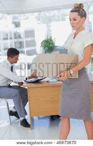 Businesswoman holding a box and her colleagues in the bottom in the office