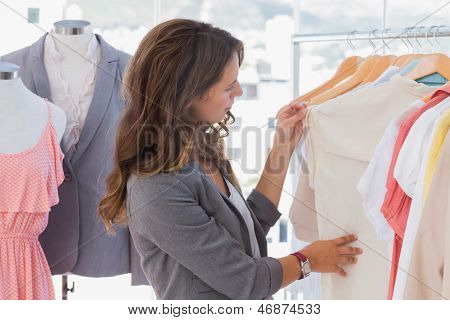 Fashion designer looking at clothes rail in her studio