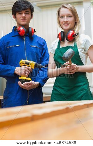 Woodworking students standing before a workbench and holding a driller and a hammer