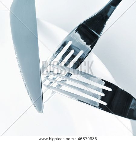 closeup of a plate, knife and forks on a set table with a white tablecloth