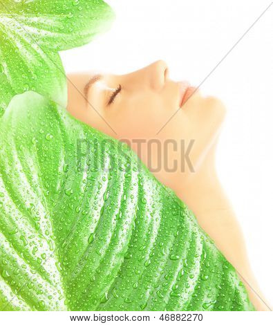 Side view on beautiful woman with closed eyes covered big fresh green leaves with dew drops isolated on white background, enjoying day spa