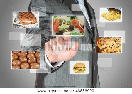 Businessman pushes touch screen button with salad