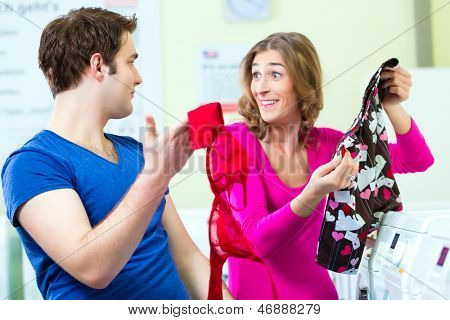 People in a launderette, washing their dirty laundry and have mistaken it, in the background are washing machines