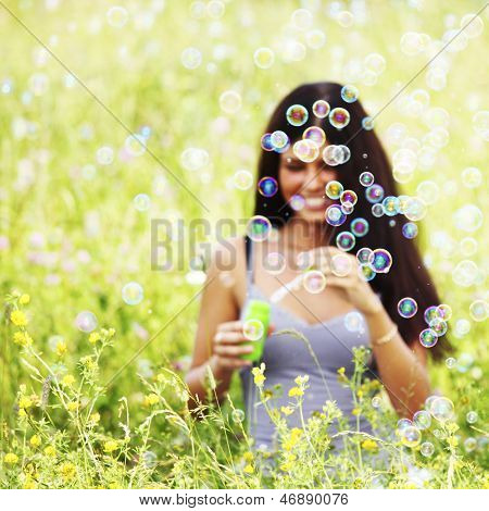 happy woman smile in green grass soap bubbles around