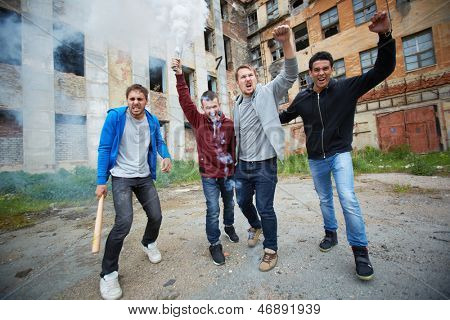 Portrait of dangerous guys exploding burning bottles