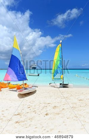 Boats for rent on Caribbean beach with cruise ship in background