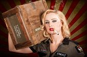 image of pinup girl  - Grunge WWII military pinup girl with 1940s blond hair style and makeup carrying weapons ammunition box on shoulder in vintage army fashion - JPG