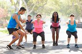 stock photo of squatting  - Group Of People Exercising Street With Personal Trainer - JPG