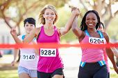 picture of victory  - Two Female Runners Finishing Race Together - JPG