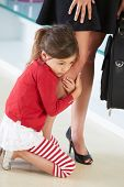 Daughter Clinging To Working Mother's Leg
