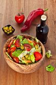 image of iceberg lettuce  - Bowl made of olive wood filled with cos and iceberg lettuce salad with paprica carrots tomatoes and green olives on wooden table - JPG