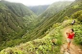 Hiking people on Hawaii, Waihee ridge trail, Maui, USA. Young woman and man hikers walking in beauti
