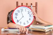 stock photo of overwhelming  - Tired child sleeping on a desk full of books and holding a clock in place of her face to symbolize tiredness after studying too much - JPG