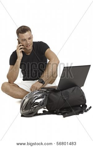 Casual young man sitting in tailor seat, talking on mobilephone, having laptop, helmet and backpack.