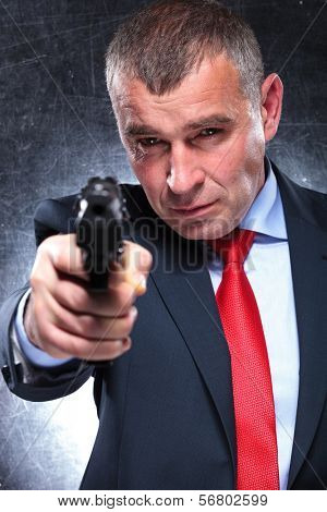 serious old killer in suit and tie pointing his gun to the camera