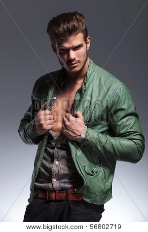 portrait of a fashion man pulling his shirt and jacket to reveal his muscular chest