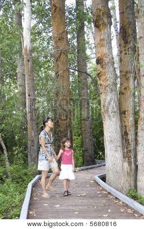 Mother and daughter walks in the woods.