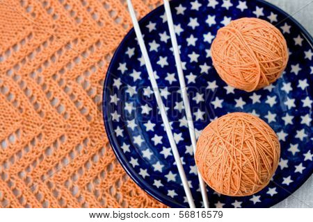 Orange balls, knitted pattern and knitting nedles