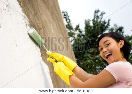 Cheerful Woman Painting Exterior Wall
