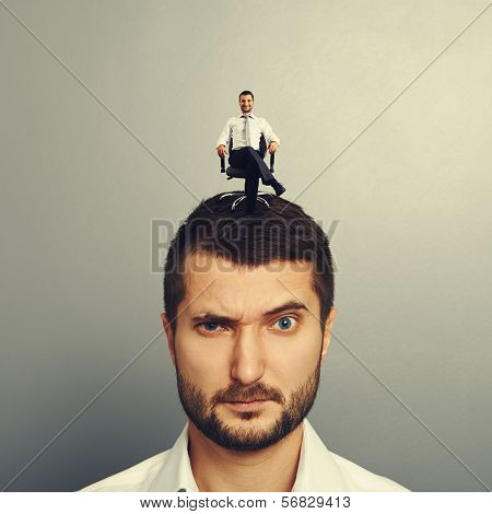 portrait of displeased man with small happy man on the head