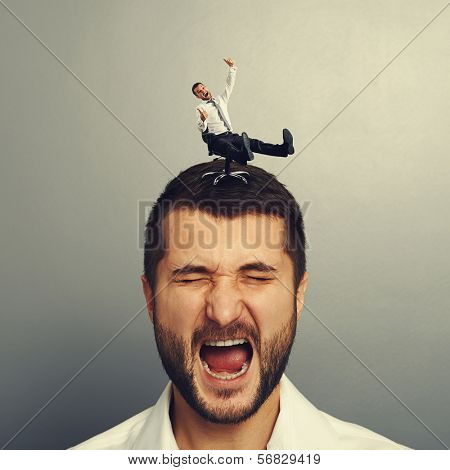 portrait of displeased screaming man with small happy man on the head