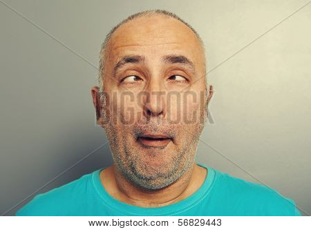 portrait of funny senior man in blue t-shirt over grey background