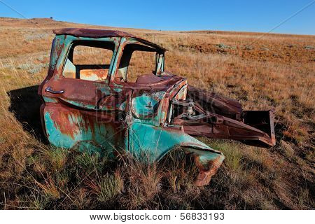 Wreck of a rusty old pickup truck out in the field
