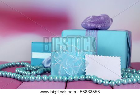 Gift boxes with blank label and chaplet on table on bright background