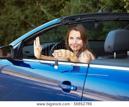 Smiling Caucasian Woman Showing Key In A Cabriolet