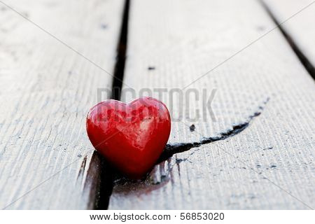Red heart in crack of wooden plank. Symbol of love, Valentine's Day, a crack may symbolize a broken heart.