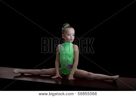 Little Adorable Gymnast In Green Leotard Suit Isolated On Black Background