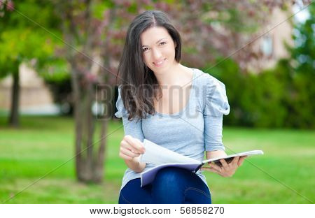 Young female student reading a book in a park