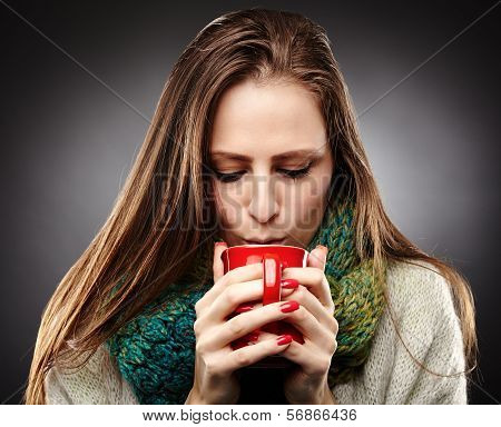 Woman With Flu Wrapped Up In A Scarf And Drinking Hot Tea