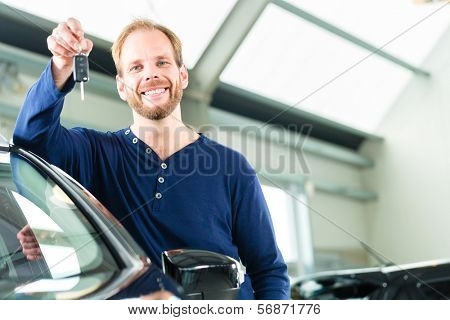 Young man beside a new car in car dealership, obviously he is buying the auto, or making a test drive and holding the keys in hand