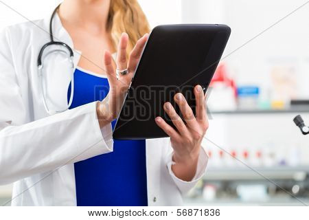 Young female doctor standing in clinic reading a file or dossier on the tablet computer