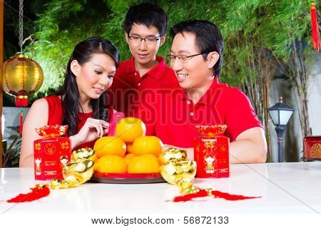 Friends family celebrate Chinese new year traditional with gift, wearing red shirts