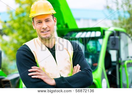 Builder or driver standing in front of construction machinery on building site