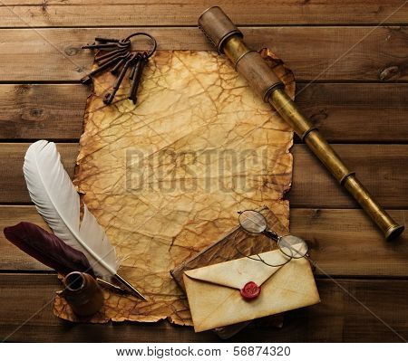 Old keys, spyglass and writing accessories on old blank paper over wooden background